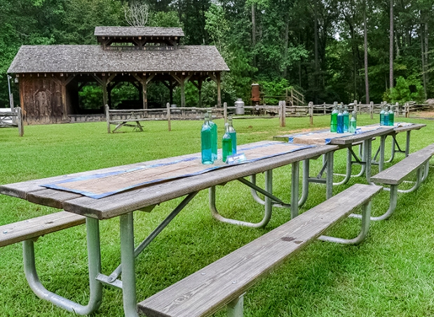 Picnic tables with hand painted reserved signs, watercolor runners. Wine bottles filled with water in different shades of blue as centerpieces.
